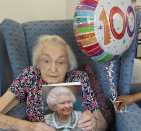 Doris holding birthday card from HM Queen