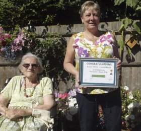 Karen White winner of Gardener of the Year, Fremantle in Bloom, holding her certificate between two female residents